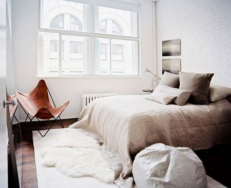 white_brick_bedroom_no_headboard_sheepskin_butterfly_chair_chouse_home