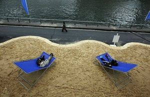 748581_people-relax-on-giant-deckchairs-as-paris-plages-opens-along-banks-of-the-seine-river-in-paris
