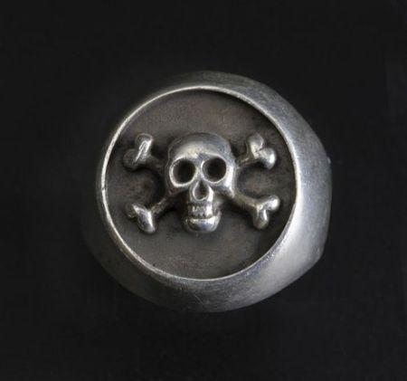 Bague en argent avec sceau figurant un crâne et tibias croisés.