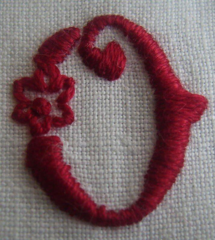 O petite fleur, brodé en rouge sombre sur un petit coeur