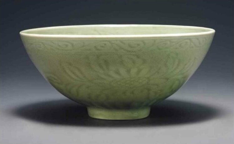 A fine early Ming Longquan celadon carved deep bowl , Yongle period (1403-1425)
