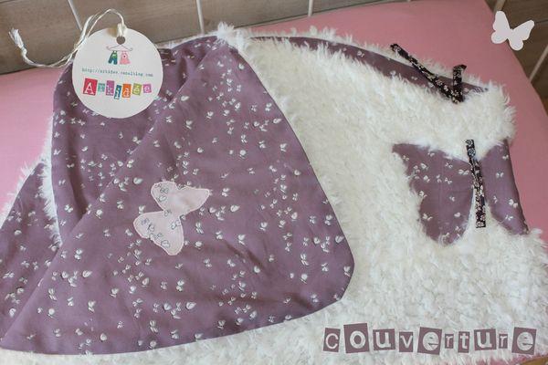 Couverture Papillon pliée sur lit