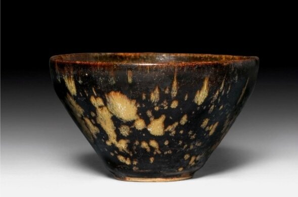 A small tortoise-glazed Jizhou bowl with prunus decoration at the inside. China, Song dynasty