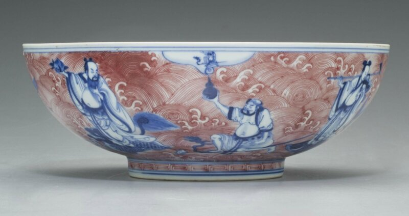 An underglaze blue and copper-red 'Immortals' bowl, Qianlong six-character seal mark in underglaze blue and of the period (1736-1795)
