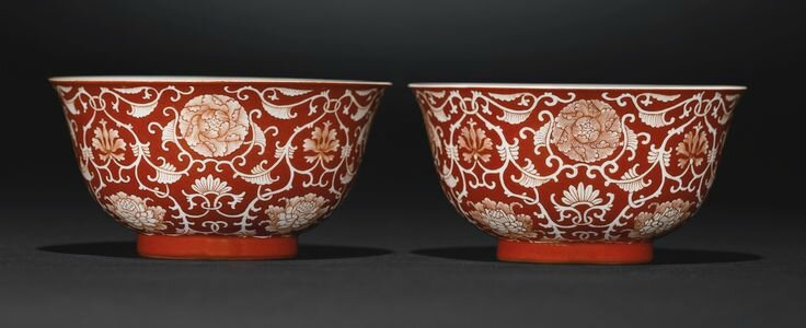 A fine pair of coral-ground reserve-decorated 'Lotus' bowls, Qianlong seal marks and period