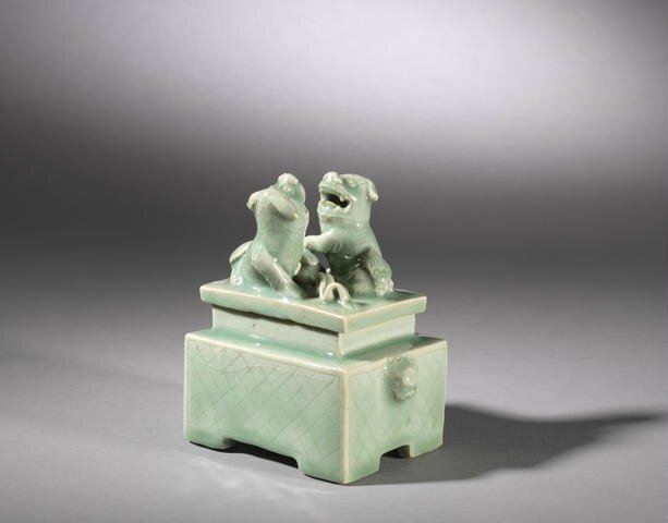 A celadon-glazed 'Buddhist lion' rectangular box and cover, Mid Ming Dynasty, 15th/16th century. Photo Bonhams