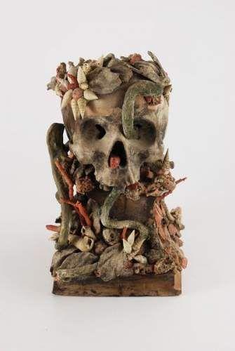 Vanité en terre cuite et corail représentant un crâne envahi par la végétation.