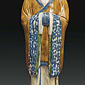 A large blue and sancai-glazed pottery figure of a court official, China, Tang dynasty (AD 618-907)