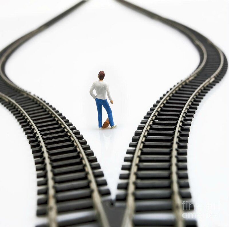3-figurine-between-two-tracks-leading-into-different-directions-symbolic-image-for-making-decisions-bernard-jaubert