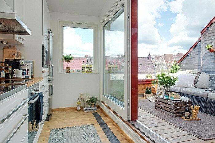 amenagement-terrasse-tropezienne-en-bois-composite-une-cuisine-qui-s-ouvre-sur-un-coin-détente-en-plein-air-table-en-palette-canapé-confortable