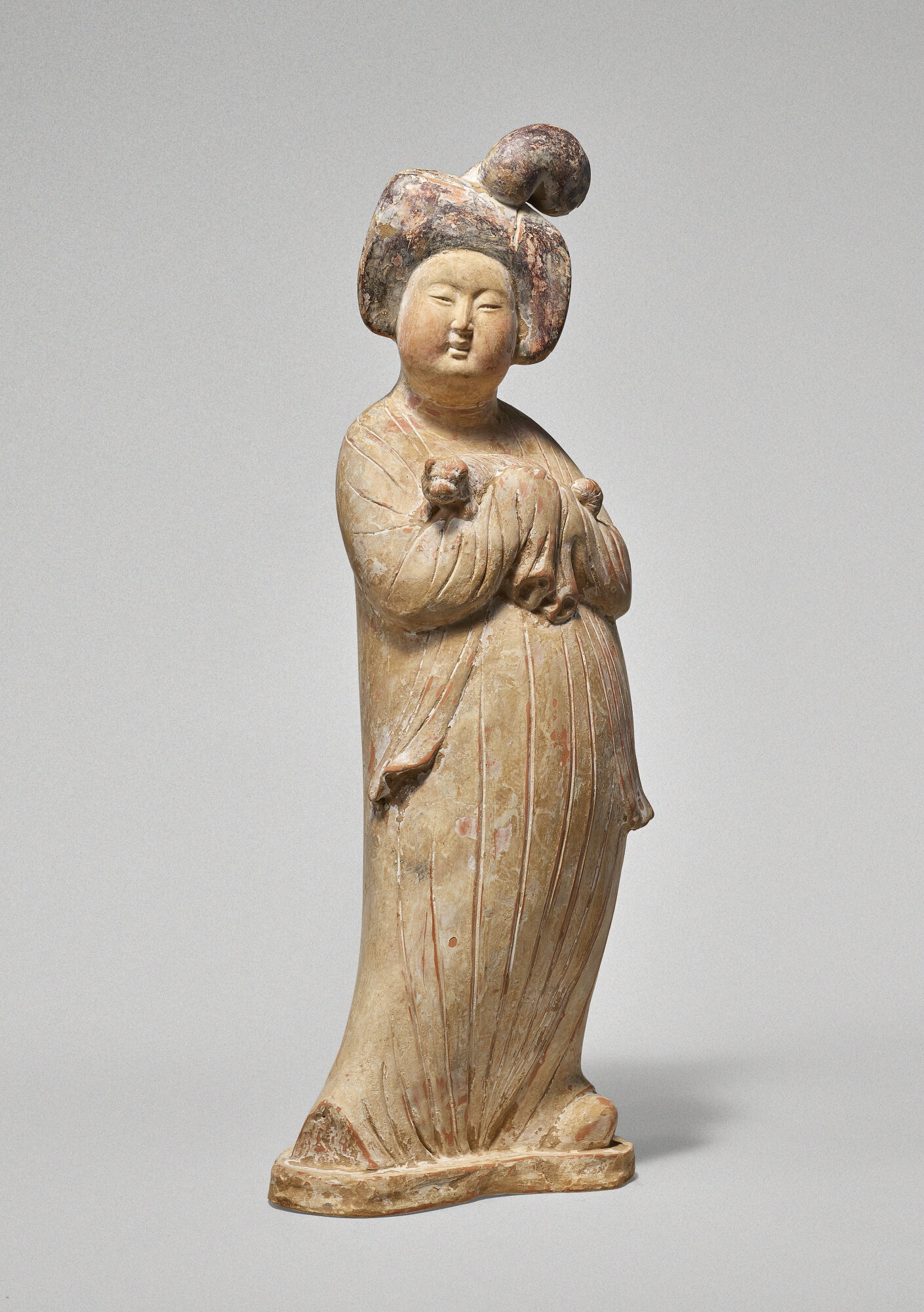 A rare and well-modeled painted pottery figure of a lady holding a dog, Tang dynasty (618-907)