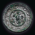 A silvery bronze 'Lion and Grapewine' mirror, Tang dynasty (AD 618-907)