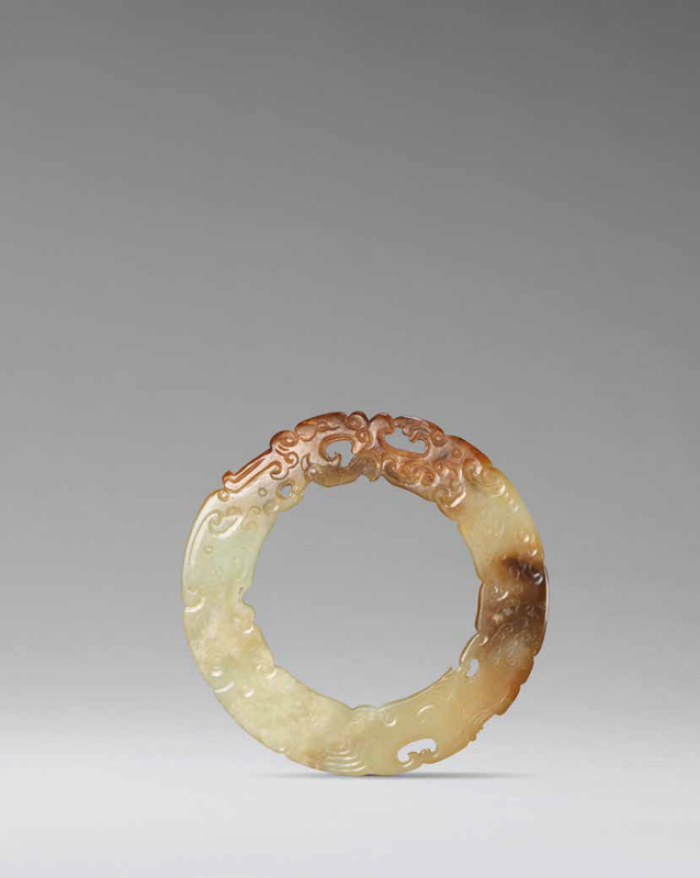 A rare archaistic pale green and russet jade 'double-dragon' disc, bi, Ming Dynasty (1368-1644)