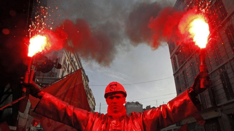 Attali-an-arcelor-mittal-steel-worker-dressed-in-a-protective-work-suit-holds-flares-as-he-demonstrates-over-pension-reforms-in-marseille_2440080