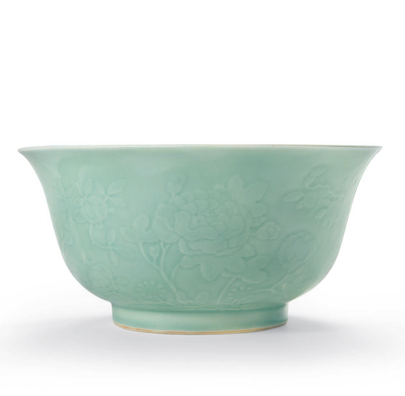 A rare large celadon-glazed relief-decorated bowl, Qianlong six-character seal mark in underglaze blue and of the period (1736-1795)