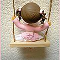 petite fille en porcelaine froide sur une balançoire