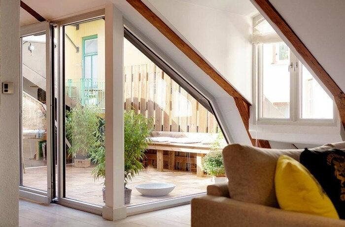 terrasse-tropezienne-composite-un-canapé-en-bois-avec-des-coussins-carrelage-plantes-verte-idee-amenagement-terrasse
