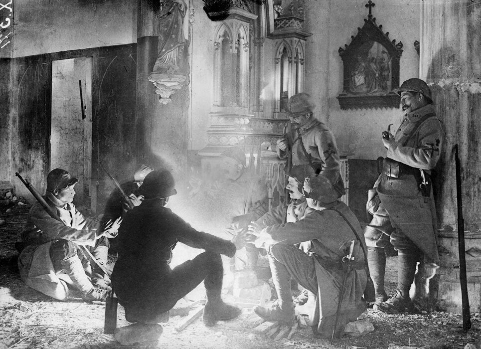 French soldiers chatting around a fire lit inside a damaged Church near Saint-Mihiel, France, 1916